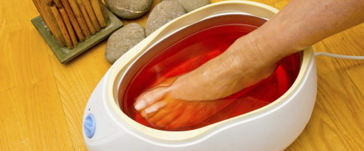 woman foot treatment in paraffin bath at the spa